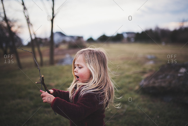 Little girl playing with sticks in backyard
