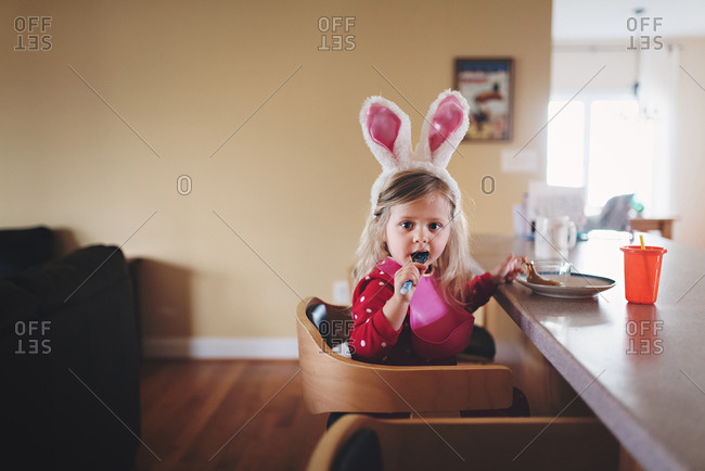 Girl in rabbit headband eating at counter