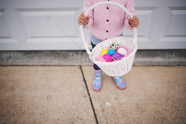 Child holding Easter basket with eggs