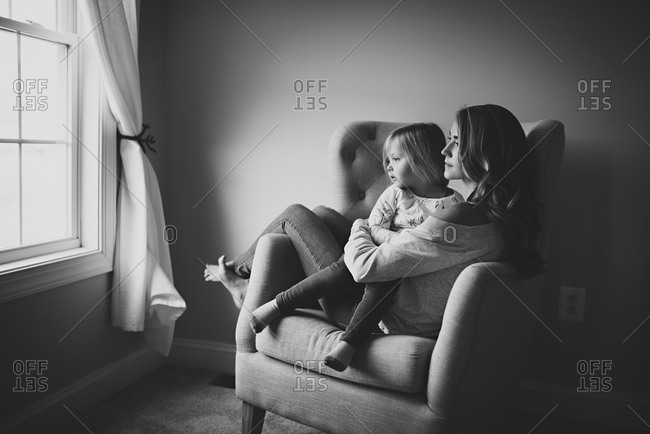 Woman sitting in chair with toddler daughter by window
