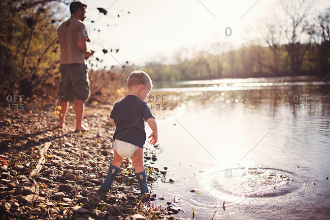 Toddler boy in diaper and boots on riverbank with father