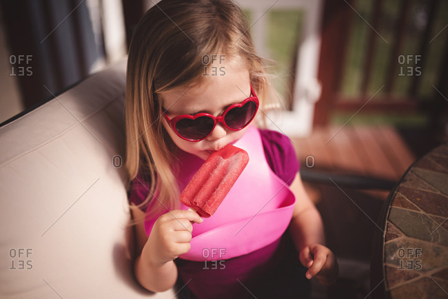 Toddler girl in heart sunglasses eating a popsicle