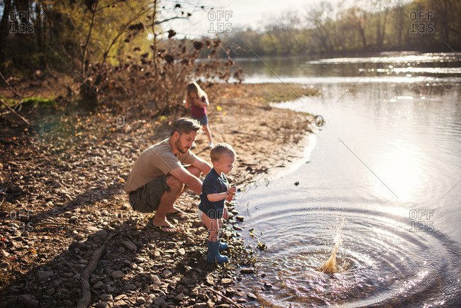 Father playing with two young children on riverbank