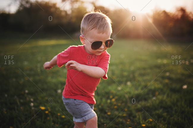 Toddler boy in sunglasses running in grass at sunset