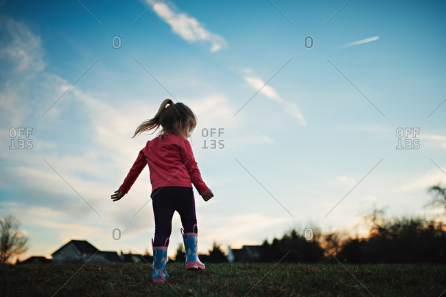 Back view of toddler girl in rubber boots at sunset