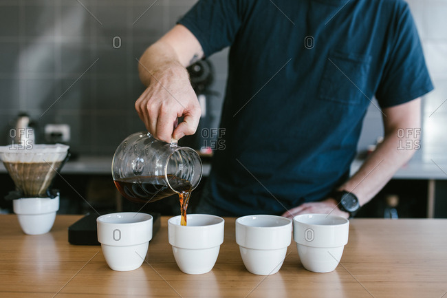 Man pouring cups of coffee at coffee shop