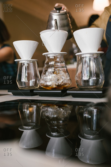 Barista pouring water to make coffee in glass cups