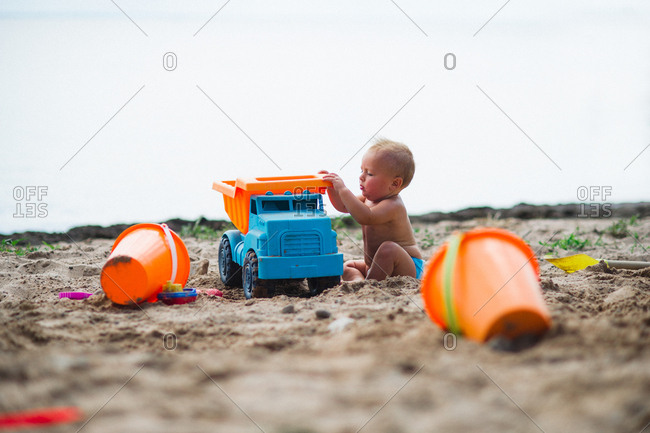 Baby boy playing with toy truck on sandy beach