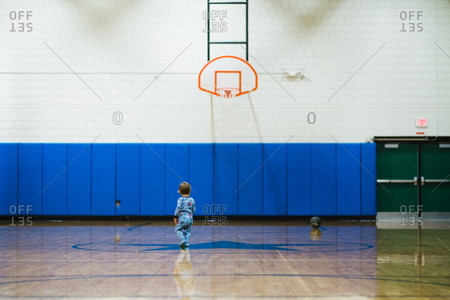 Toddler boy walking alone on basketball court