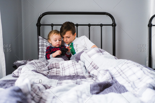 Boy sitting in bed with his baby brother who is playing with mobile phone