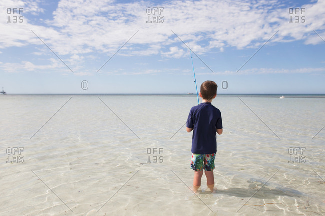 Boy fishing in shallow water