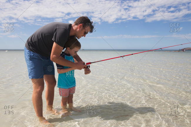 Father showing his son how to use fishing reel