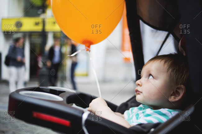 Baby in stroller holding balloon