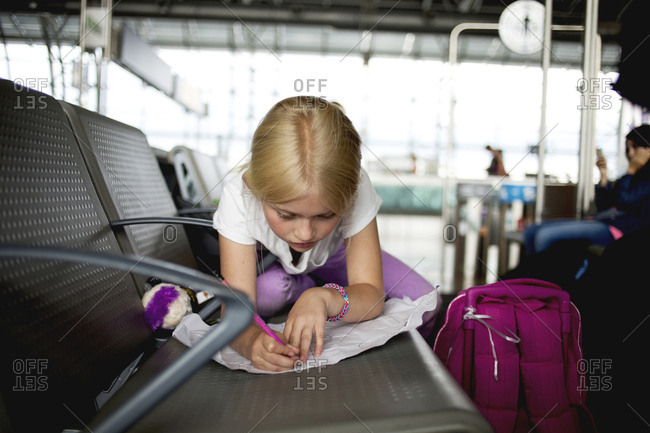 Girl writing in an airport