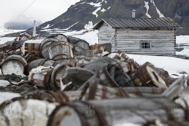 Wooden cabin by pile of old broken barrels on snowy ground