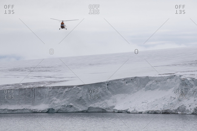 Helicopter flying over glacial cliff on the coast of Franz Josef Land