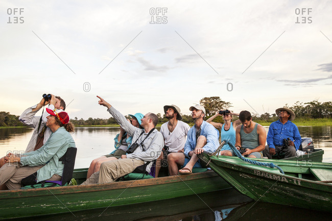 Amazonas, Brazil - February 25, 2015: Group of tourists spotting a bird in the jungle canopy from their canoe on the Amazon River