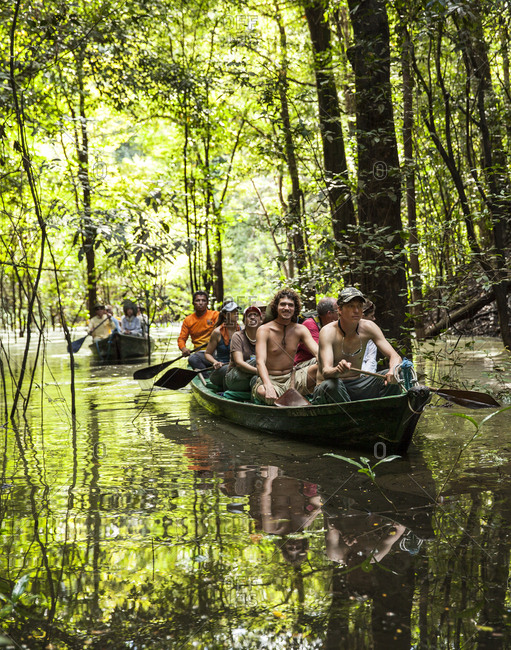 Tourists paddling a canoe through a dark and narrow spot in the Amazon Jungle