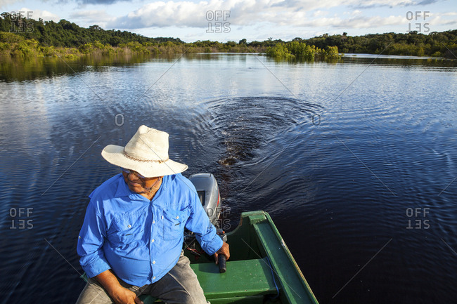 A guide in the Amazon pilots a motorized canoe along the river