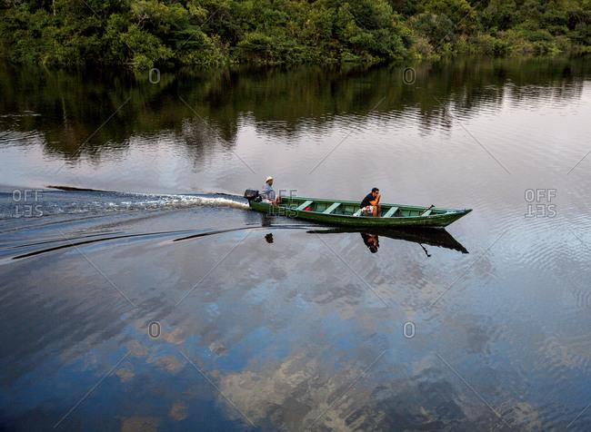 Men riding in a motorized canoe in Amazon