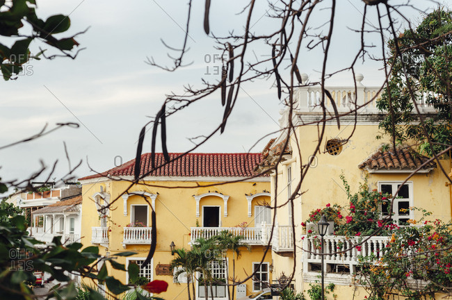 Front view of a typical colonial building surrounded by trees in Cartagena de Indias, Colombia