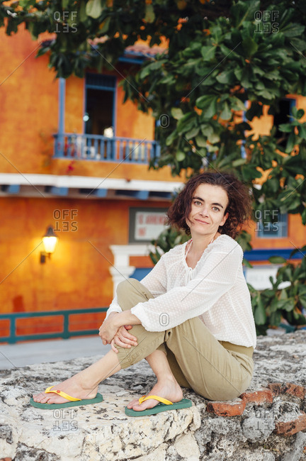 Woman seated on a stone wall in the old town of Cartagena de Indias, Colombia