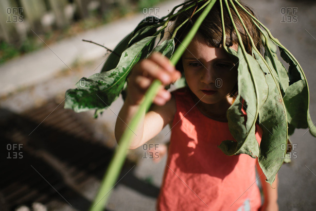 Girl playing with a branch with leaves outside in a parking lot