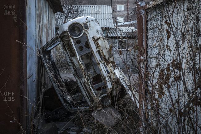 Car chassis acting as a fence between houses