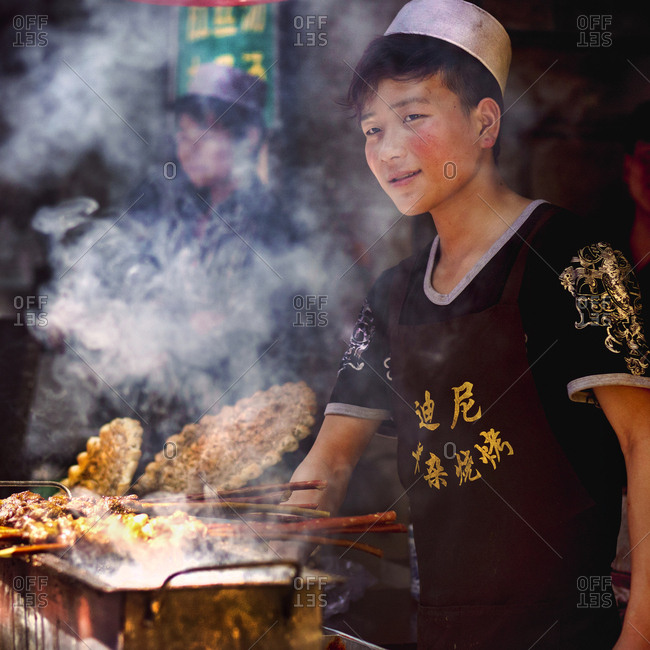 Muslim Quarter, Xi'an, China - April 25, 2016: Boy grilling lamb on skewers