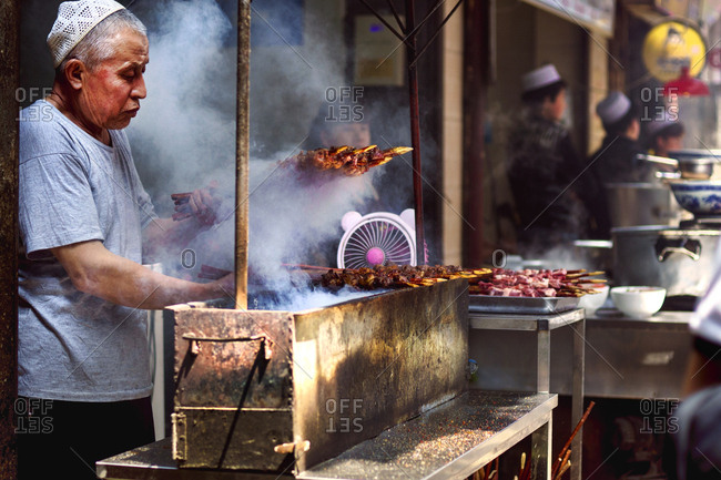 Muslim Quarter, Xi'an, China - April 25, 2016: Man grilling lamb on skewers