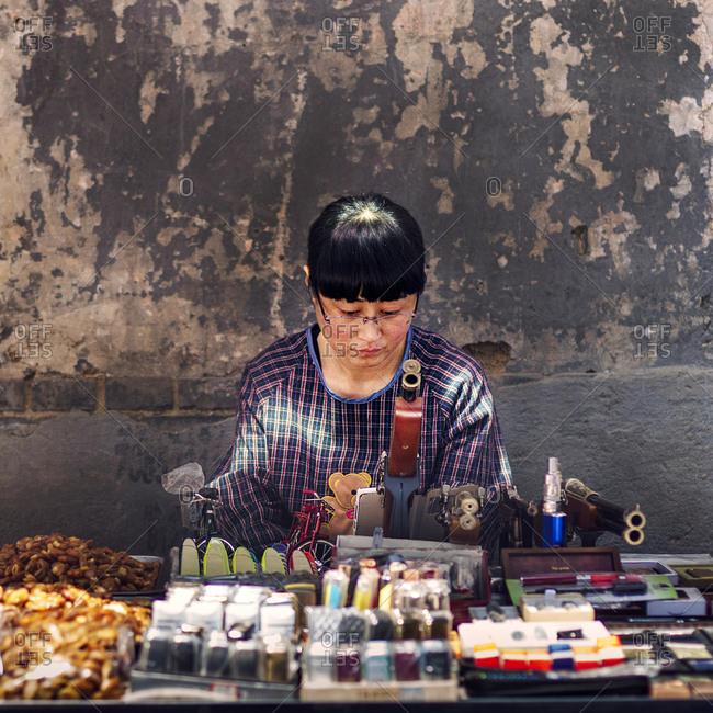 Muslim Quarter, Xi'an, China - April 25, 2016: Woman selling souvenirs
