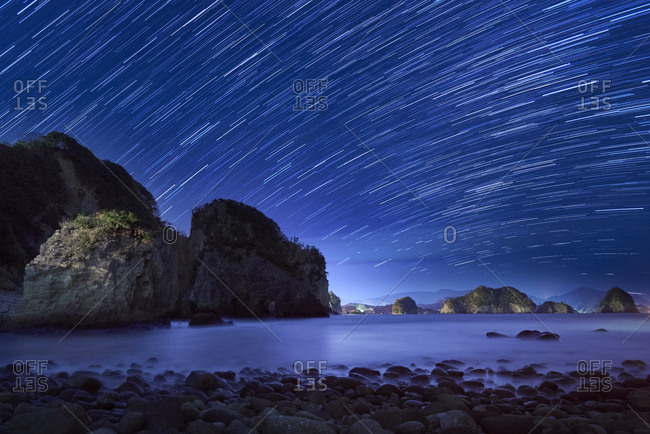 Star trails at night over sea and rock formations at Futo coast, Shizuoka Prefecture, Japan