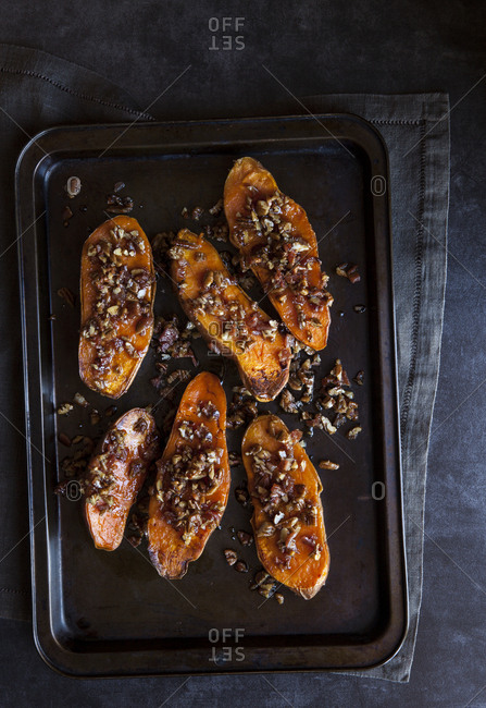 Baked sweet potatoes with pecans and maple syrup on a baking tray