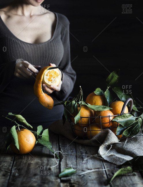 Woman peeling a orange with a knife