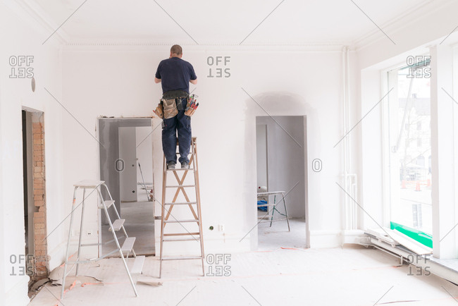 Man on a ladder making home improvements in a room