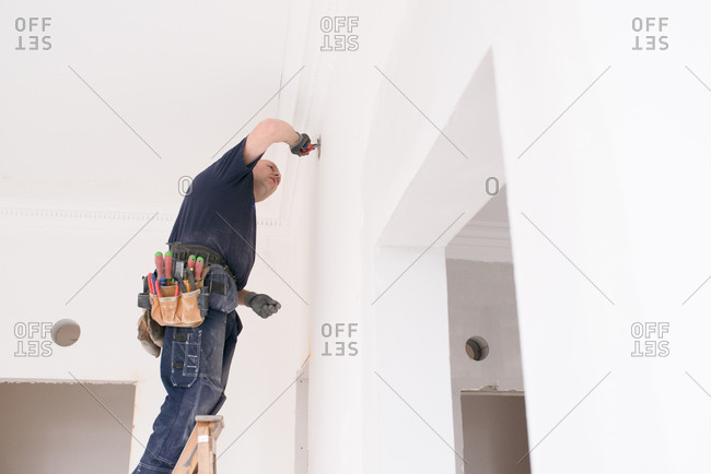 Man using pliers to work on a wall in a home