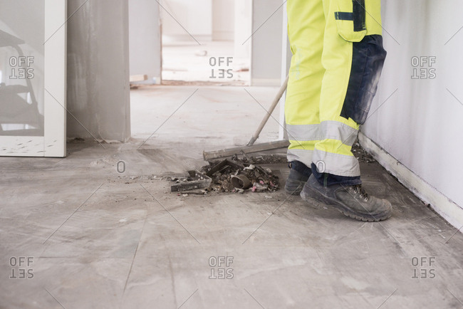 Worker sweeping up debris at a home improvement site