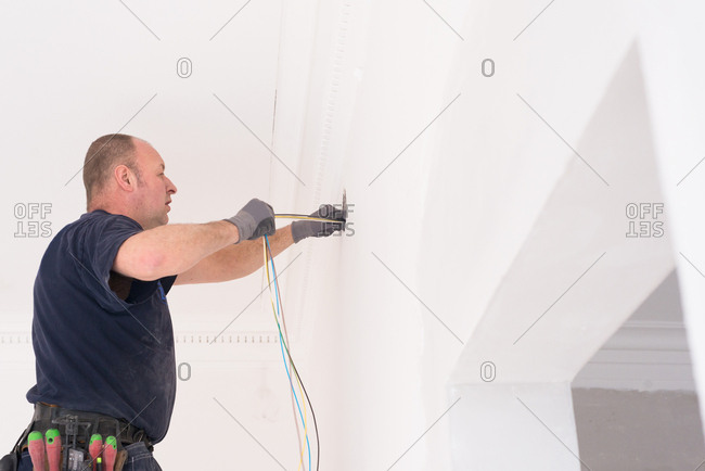 Electrician pulling wiring through a hole in a wall