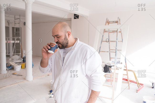 Worker drinking coffee at a home improvement site