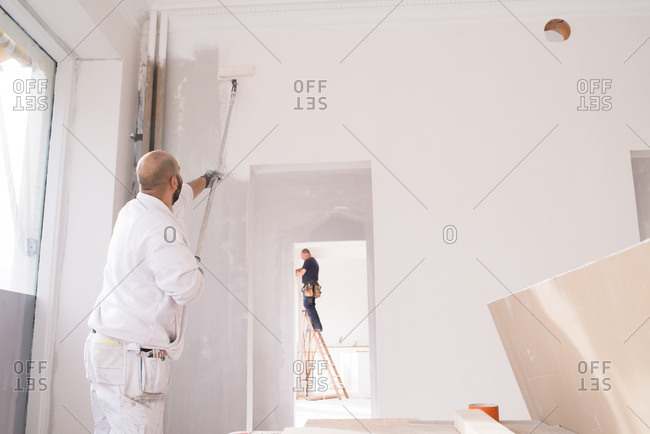Man painting the while of a house while an electrician works