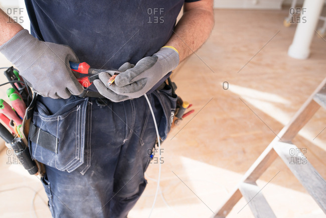 Electrician cutting wires on a home improvement site