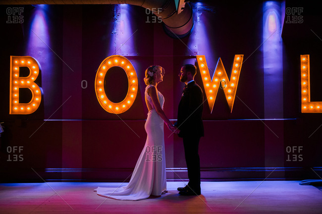 Bride and groom standing together in front of a retro sign
