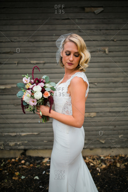 Bride in her gown holding a bouquet in front of a weathered wall