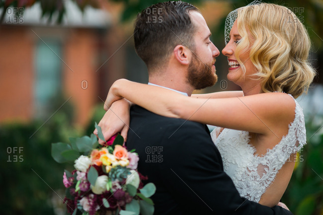 Bride and groom embracing and laughing together