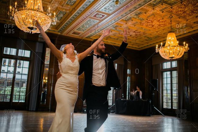 Bride and groom walking across the dance floor in an elegant ballroom