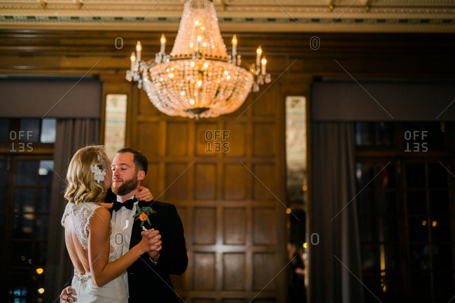 Newlywed couple dancing together under an elegant chandelier