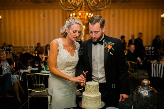 Newlywed couple cutting their wedding cake together