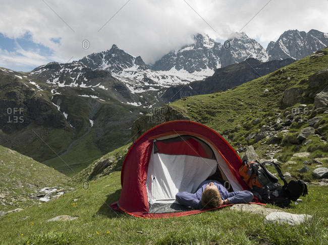 Hiker reclines in tent, alpine meadow, mountains