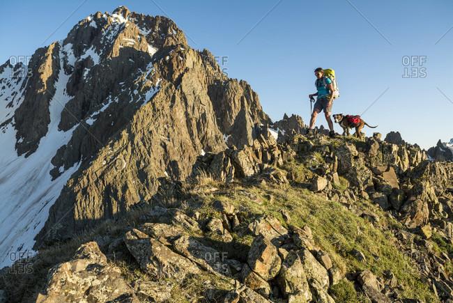 A Woman With Her Dog Hiking On Blaine Peak Below Mount Sneffels, Colorado