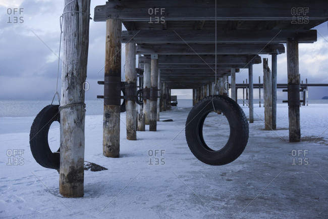 Tire Swing Hanging From A Pier On Lake Tahoe During Winter